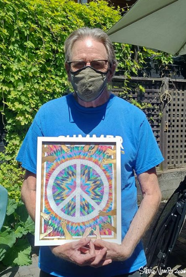 A snapshot of an older white man wearing a face mask and glasses and blue shirt, posing in the bright sun with a framed peice of artwork depicting a number of hands stitching together a quilt with a peace sign on it.
